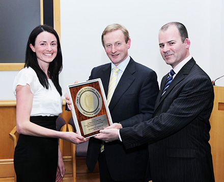 The Taoiseach presenting an Excellence Award to our team